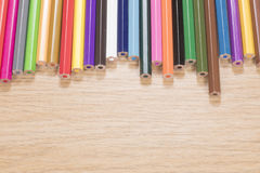Colorful collection of wooden pencil crayons. Arranged in an uneven line on a wooden table with copy space Royalty Free Stock Photo