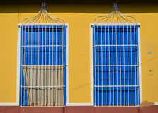 Colorful Colonial Windows. Colorful cononial and simetric blue windows in a yellow house in Trinidad, Cuba Stock Photo