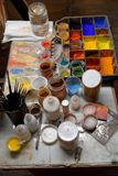 Colorful color powder pigments  at a workplace of an artist. Artist workplace,  pallet various  colorful powder pigments, brushes,  bowls and water Royalty Free Stock Photo