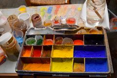 Colorful color powder pigments  at a workplace of an artist. Artist workplace,  pallet various  colorful powder pigments, brushes,  bowls and water Stock Photos