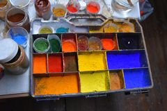 Colorful color powder pigments  at a workplace of an artist. Artist workplace,  pallet various  colorful powder pigments, brushes,  bowls and water Stock Photo
