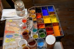 Colorful color powder pigments  at a workplace of an artist. Artist workplace,  pallet various  colorful powder pigments, brushes,  bowls and water Royalty Free Stock Images