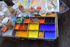 Colorful color powder pigments  at a workplace of an artist. Artist workplace,  pallet various  colorful powder pigments, brushes,  bowls and water Royalty Free Stock Photos