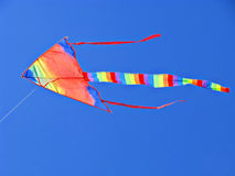 Colorful, colorful, striped kite flying in the blue sky Stock Photo