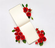 Colorful composition with sketchbook and roses. Flat lay on white table, top view Stock Photo