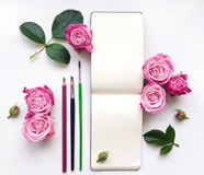 Colorful composition with sketchbook, roses and pencils. Flat lay Stock Photos