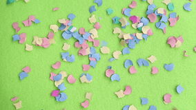 Colorful confetti falling on green rotating plate stock video