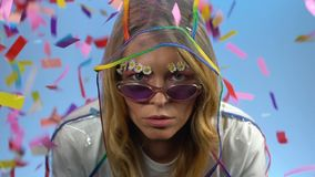 Colorful confetti falling on woman hiding in transparent raincoat, fashion. Stock footage stock footage