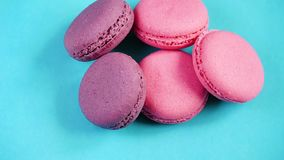 Colorful cookies or French macaroon dessert on pastel background.