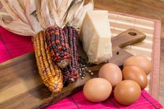 Colorful corns, cheese, eggs, decorative pepper on a wooden board Royalty Free Stock Photos