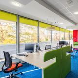 Colorful corporate interior with desks. Colorful and modern corporate interior with wood desks with green partitions royalty free stock photos