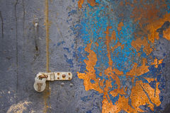 Colorful corroded metal door. Colorful corroded metal garage door padlocked shut Royalty Free Stock Photos
