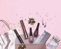 Colorful cosmetic set on peach background with gift bag, stars and gift bow, flat stock photos