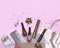 Colorful cosmetic set on violet background with gift bag, stars and gift bow, flat royalty free stock images