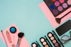 Colorful cosmetics on blue workplace with copy space. Cosmetics make up artist objects: lipstick, eye shadows, powder. Tools for make-up.Top view selective Royalty Free Stock Image