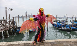 Colorful Costume. Venice, Italy- February 19th, 2012: A man disguised in a colorful costume dancing in front of the gondola's dock in Venice during the Carnival Stock Photo