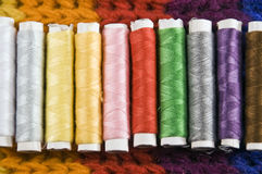 Colorful cotton reels in a row. On a colorful background Stock Photography
