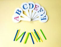 Colorful counting sticks for calculating mathematical operations for learning to count and set of letters on yellow background