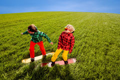 Colorful couple snowboarding on the grass in greenfield Stock Photography