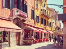 Colorful cozy street with tables of cafe at  a sunny morning, Venice, Italy.    Toned image Royalty Free Stock Image