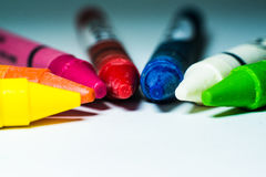 Colorful crayon sticks on white background. Focus on red, pink, and blue color stock photos