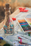 Colorful crayons, acrylic paints and bottle with wishes Stock Photos