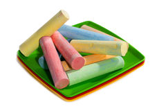Colorful crayons for drawing in colored plates. On a white background Royalty Free Stock Images