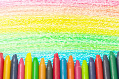 Colorful crayons and drawing of the rainbow. Royalty Free Stock Photos