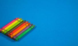 Colorful crayons lined on blue background. Royalty Free Stock Images