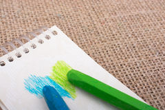 Colorful crayons on a notebook with a heart shape Royalty Free Stock Image