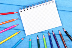 Colorful crayons and notepad on blue boards, school accessories, copy space for text Royalty Free Stock Image
