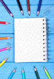 Colorful crayons and notepad on blue boards, school accessories, copy space for text. Colorful crayons and notepad for notes on blue boards, school supplies and Royalty Free Stock Photography