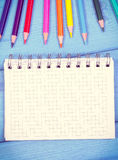 Colorful crayons and notepad on boards, school accessories, copy space for text Royalty Free Stock Image