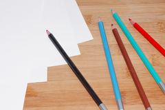 Colorful crayons and paper. On a wooden table Royalty Free Stock Images