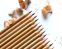 Colorful crayons and pencil shavings on white background Stock Photos