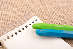 Colorful crayons placed on a notebook Royalty Free Stock Photos