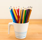 Colorful crayons in the pot. Placed on the wood desk stock photo