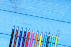 Colorful crayons, school accessories, copy space for text on blue boards Royalty Free Stock Photography