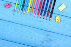 Colorful crayons, sharpener and eraser on blue boards, school accessories, copy space for text Stock Image