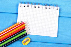 Colorful crayons, sharpener and notepad on blue boards, school accessories, copy space for text. Colorful crayons, sharpener, notepad for notes on blue boards Royalty Free Stock Photo