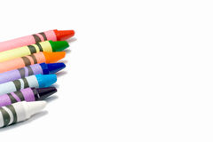 Colorful crayons on a white background with text space. Closeup of colorful crayons (the colors of the rainbow) against pure white background with text space stock image