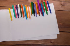 Colorful crayons with a white blank sheet of paper on a wooden b Stock Photos