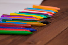 Colorful crayons with a white blank sheet of paper on a wooden b Royalty Free Stock Photos