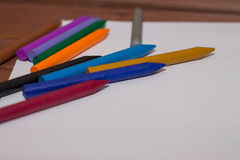 Colorful crayons with a white blank sheet of paper on a wooden b Royalty Free Stock Images