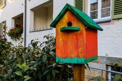 Colorful Birdhouse near the house stock photography