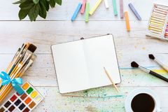 Colorful creative table with blank notebook for sketches and paints, pencil, paintbrushes set and cup of coffee on white wooden royalty free stock image
