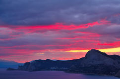 Colorful crimson sunset on the Black sea coast in Crimea, Sudak. Crimson and dark blue clouds in the sky over the mountains. Scenic rocky mountains near the sea Stock Images