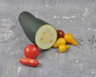 Tomatoes and zucchini on conccrete Royalty Free Stock Images