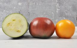 Tomatoes and zucchini on weathered wood Royalty Free Stock Photos