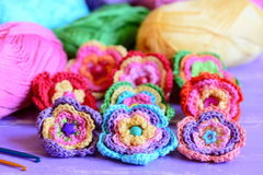 Colorful crochet flowers collection. Crochet flowers, multicolored cotton yarn, crochet hooks on purple wooden table Stock Images